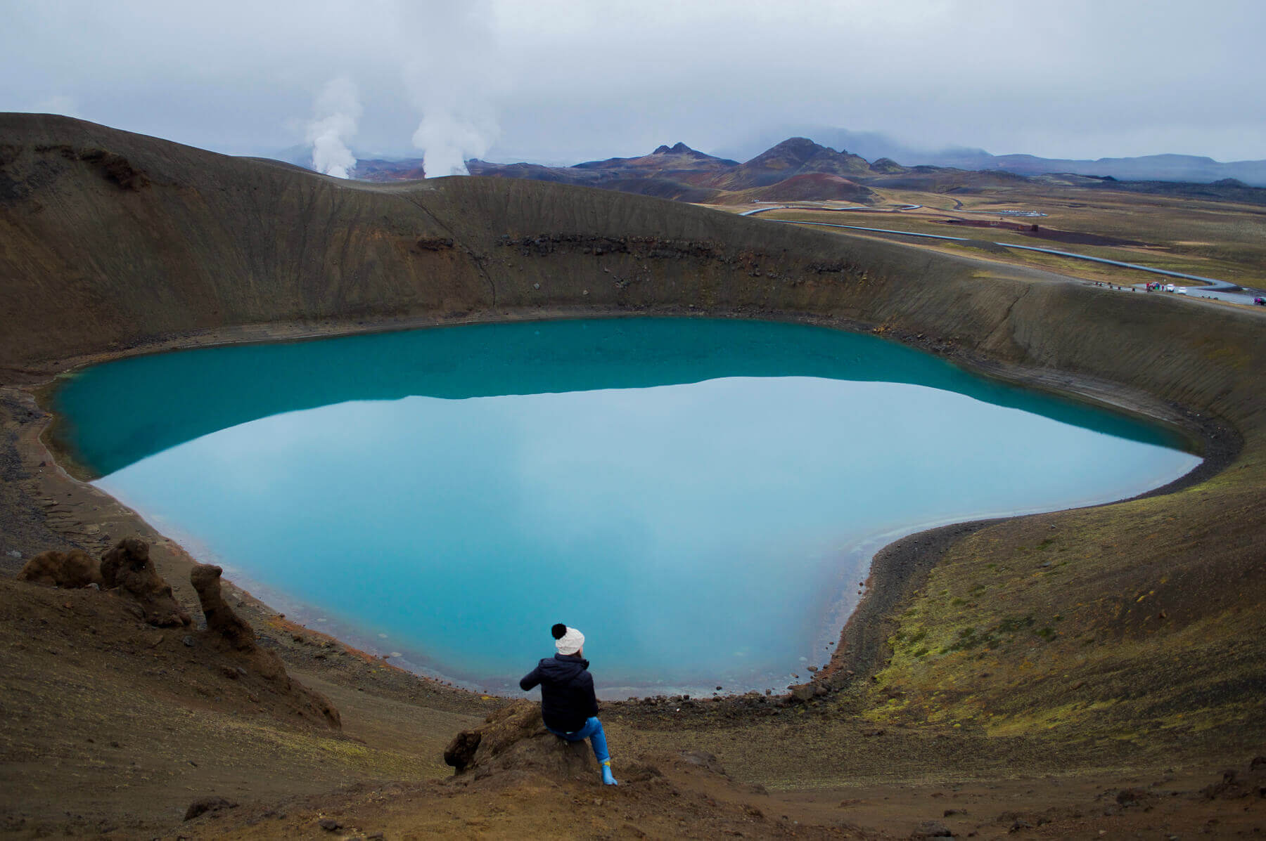 Girl overlooking a crater full of bright blue water