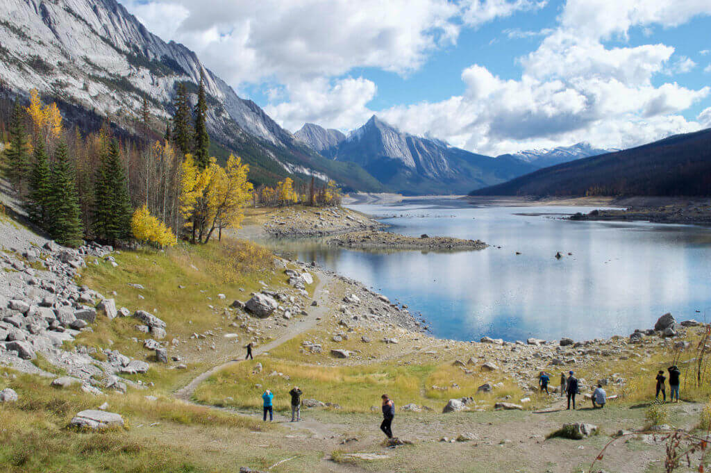People photographing a lake in the middle of the Rocky Mountains