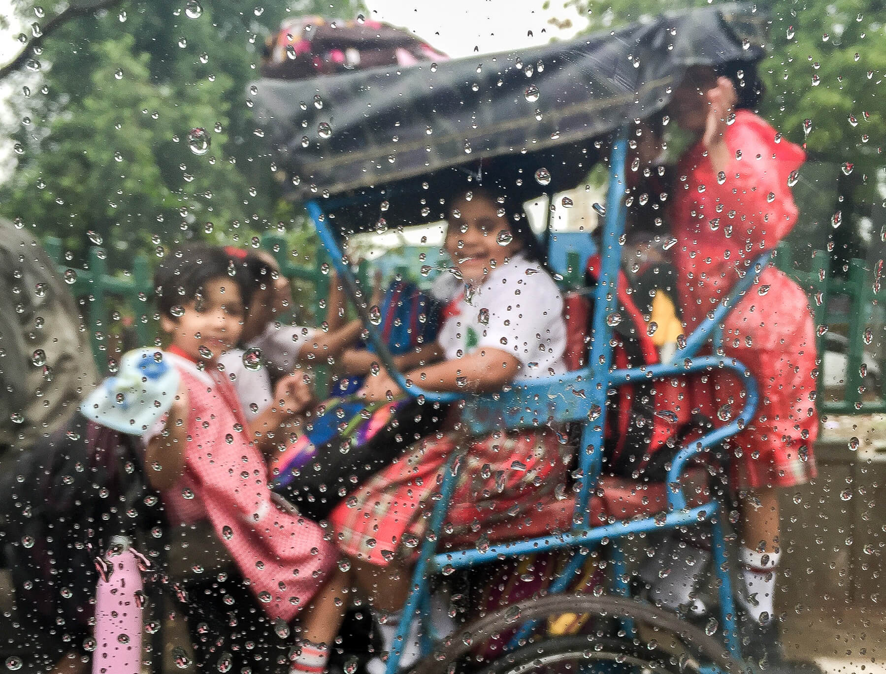 Rain on window, looking at Indian Girls on a Rickshaw