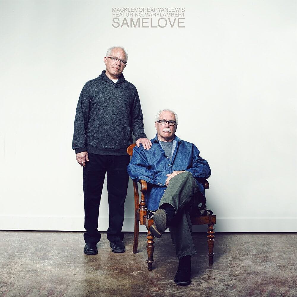 An old man sitting in a chair infront of a white wall, with another man standing next to him with his hand on his shoulder - Macklemore and Ryan Lewis, Same Love