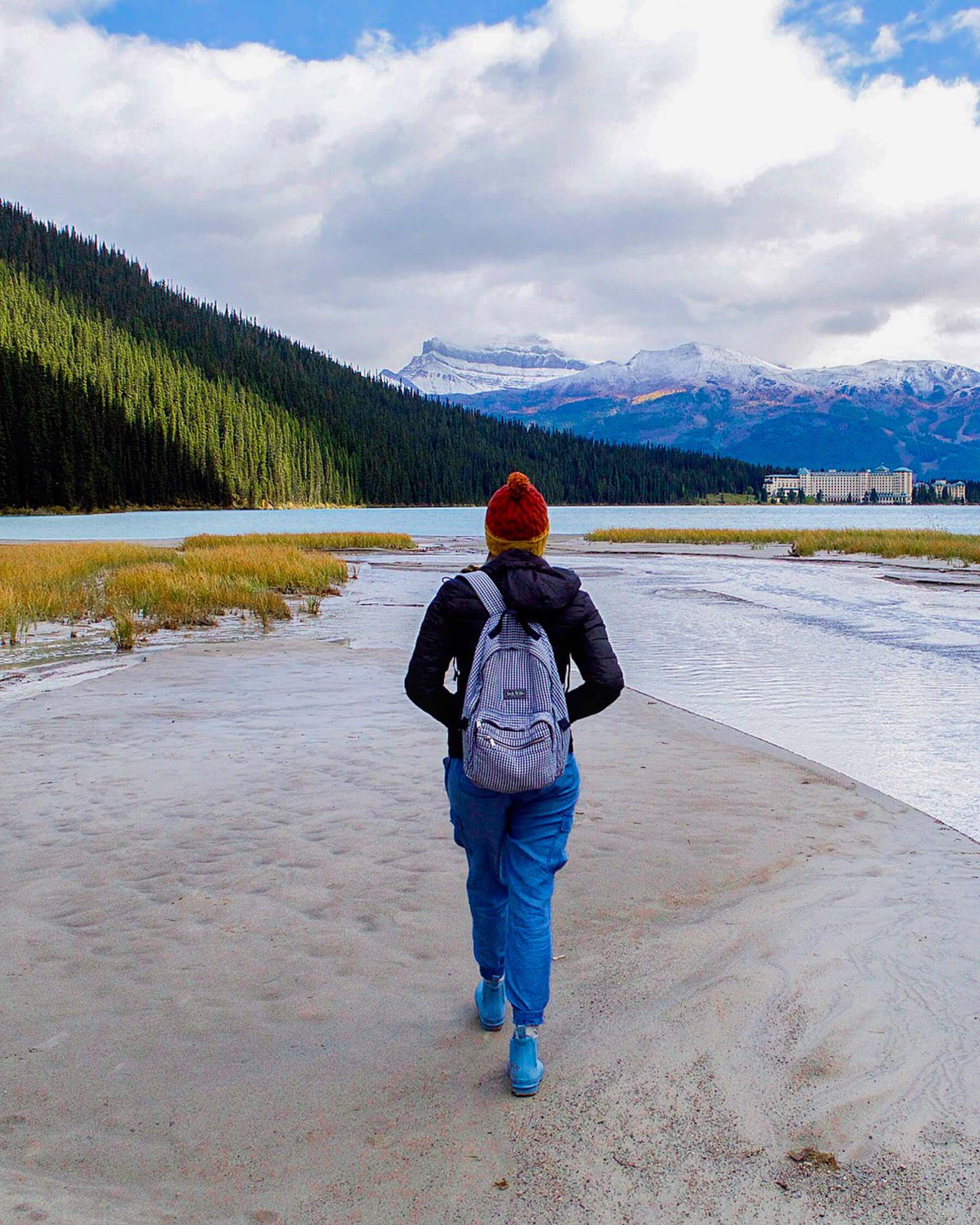Girl walking towards lake louise with hotel and mountain in the distance