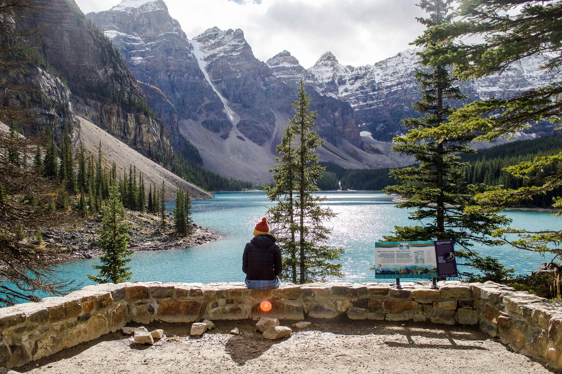 Girl sitting on ledge overlooking turquoise lake and mountains