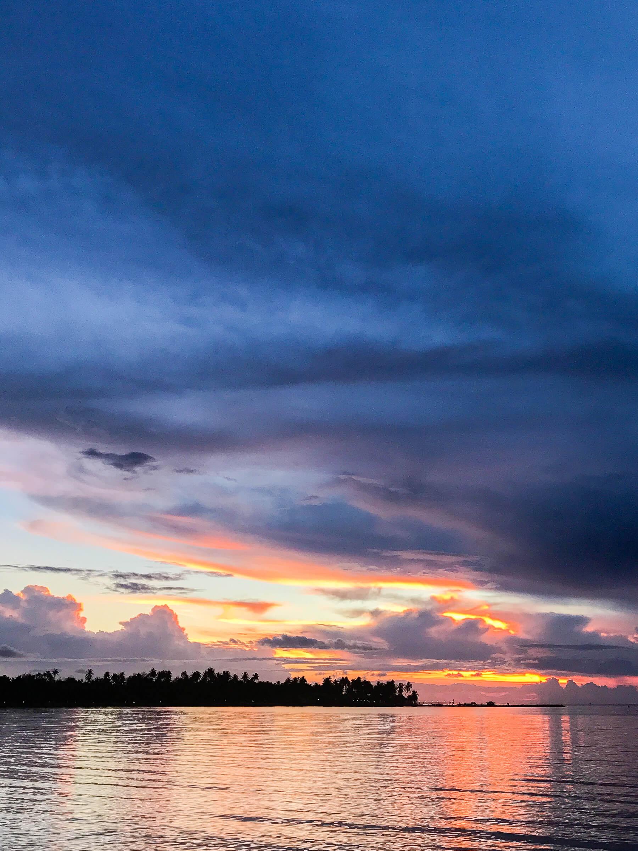 Dark blue sunrise through rain clouds, over the ocean