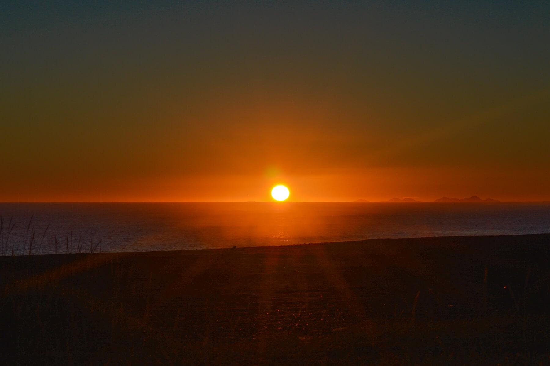 Orange sun shining over the horizon - behind the beach