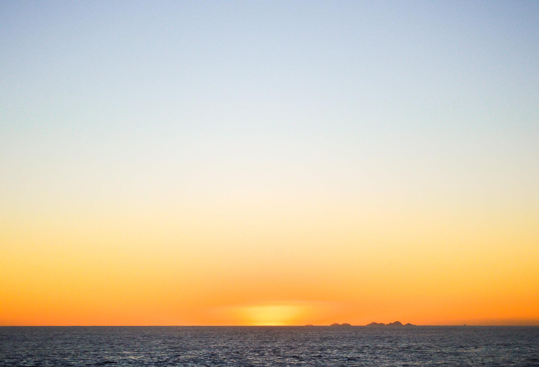 Yellow sunset steaming below the ocean