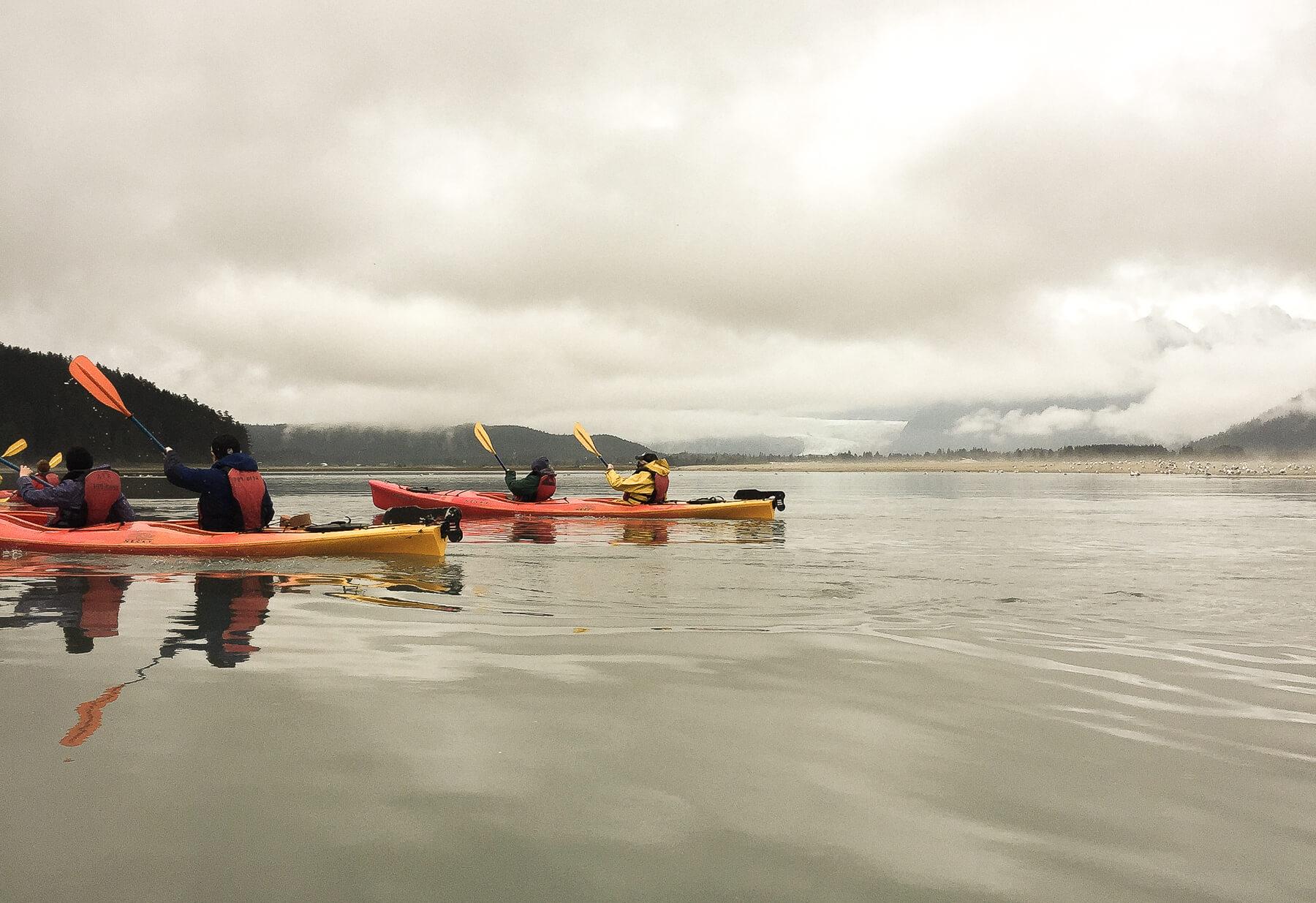People paddling 2 Sea Kayaks through a still bay