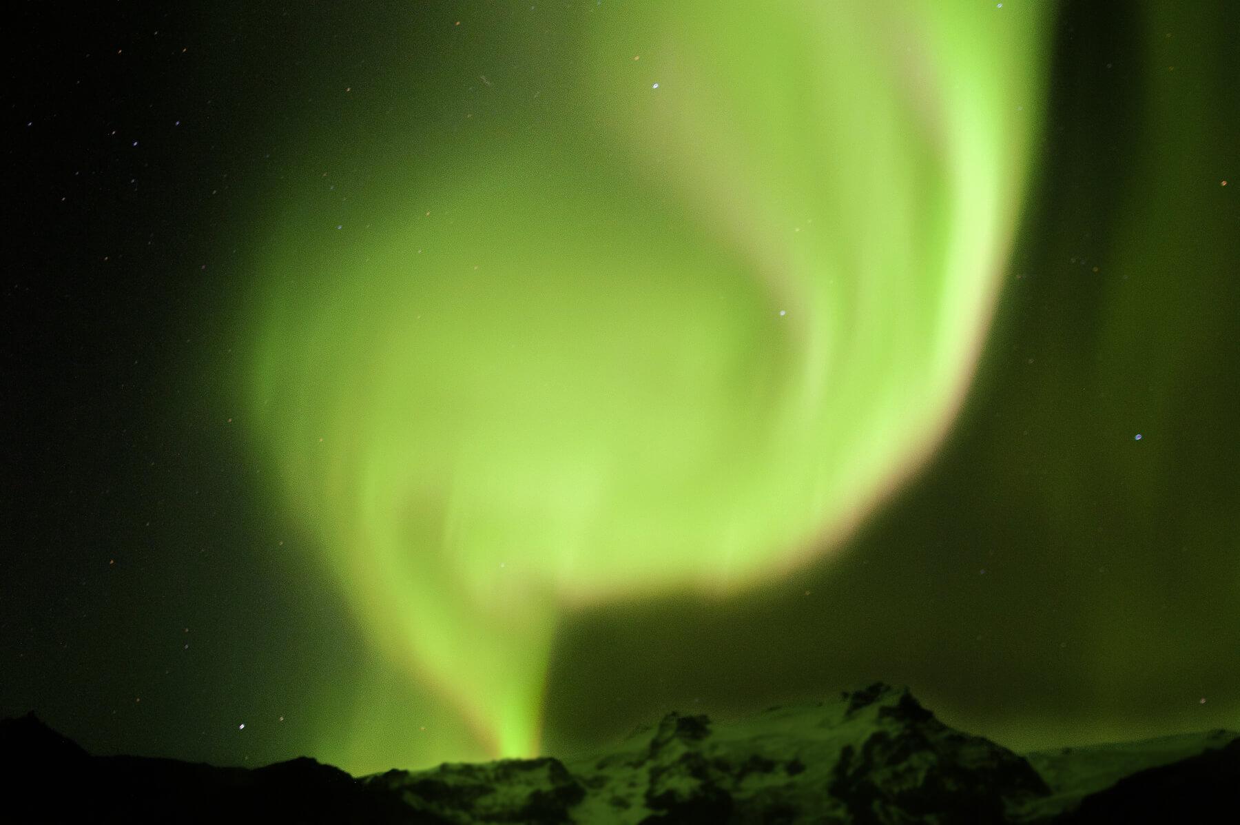 Bright, swirling green aurora heading behind a mountain peak