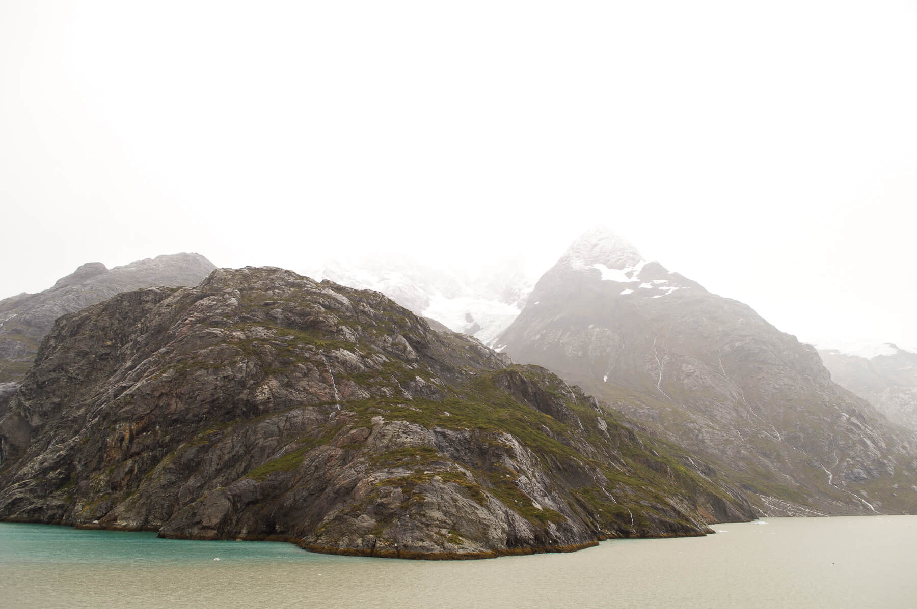 Rocky hill surrounded by turquoise Glacially fed water