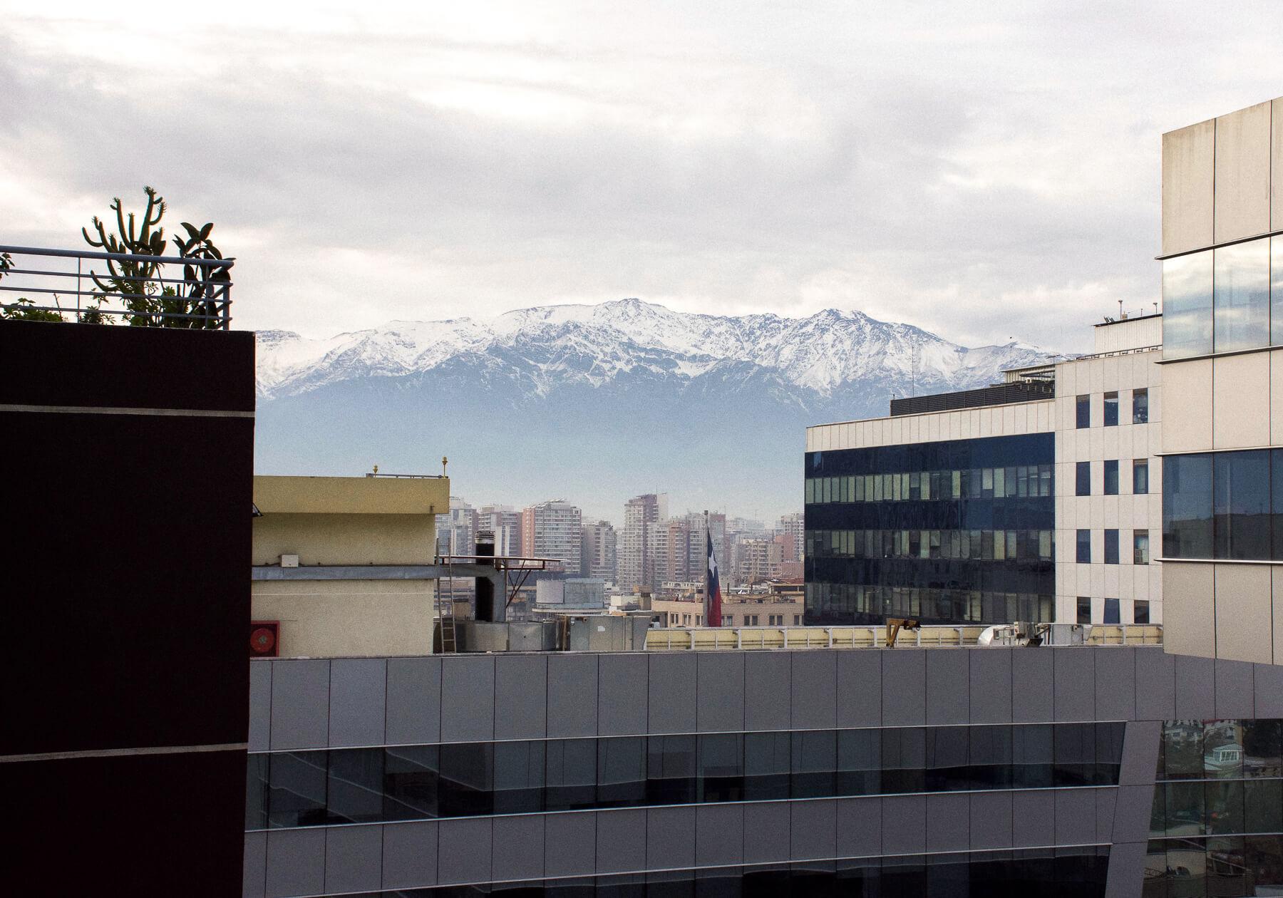 Mountain peaks appearing behind high-rise buildings in Santiago