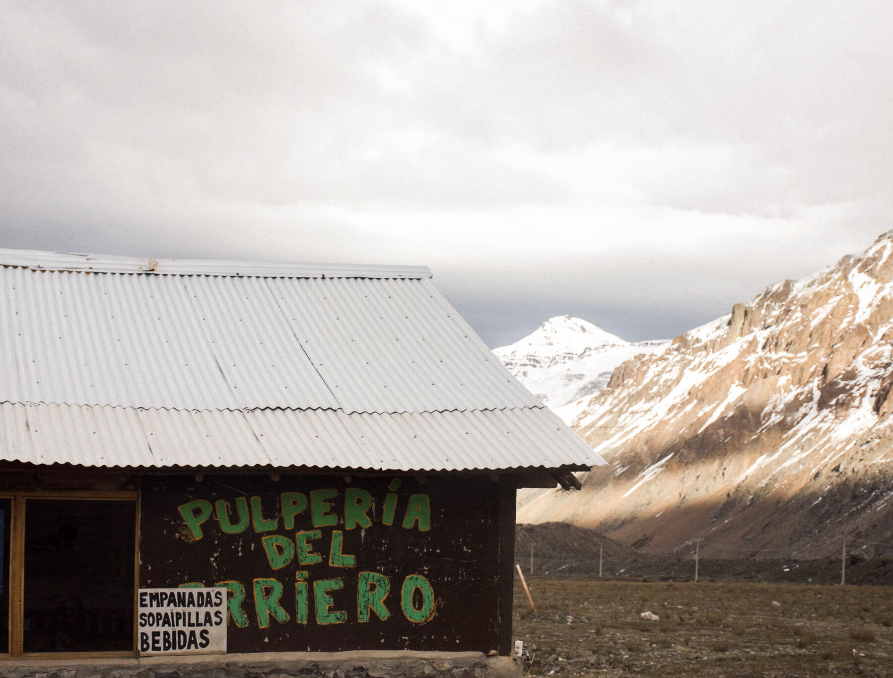 "A building with sign ""PULPERIA DEL ARRIERO"" - rocky mountains in the background"