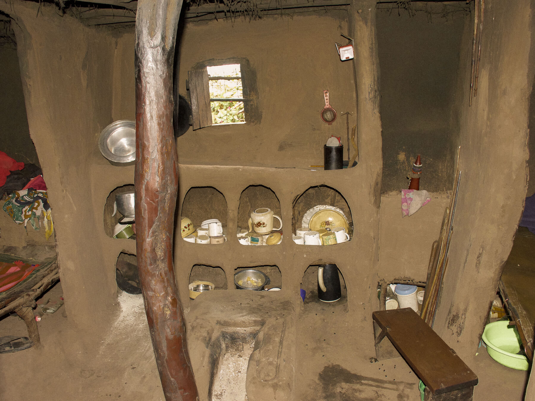 Looking inside a Maasai house at bedding made of cow skin, and kitchen and walls made of cow poo and mud