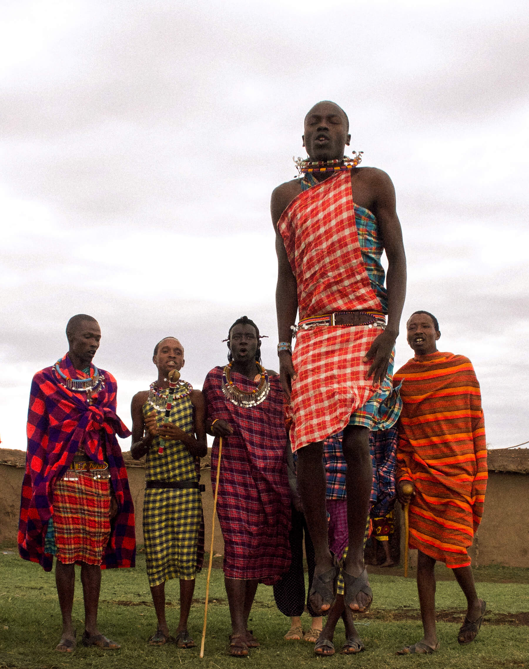A group of Maasai men in their traditional dress standing in a line behind one man that is jumping