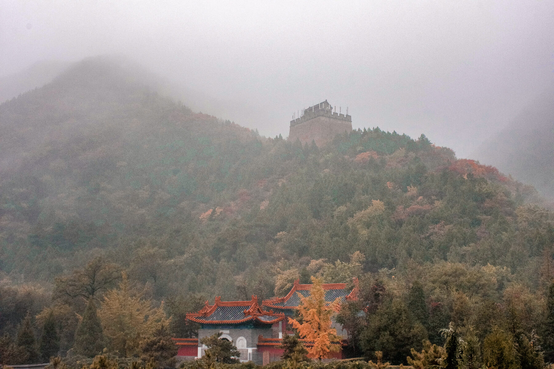 A temple at the bottom of a mountain, with the Great Wall winding up the hill behind it in the mist