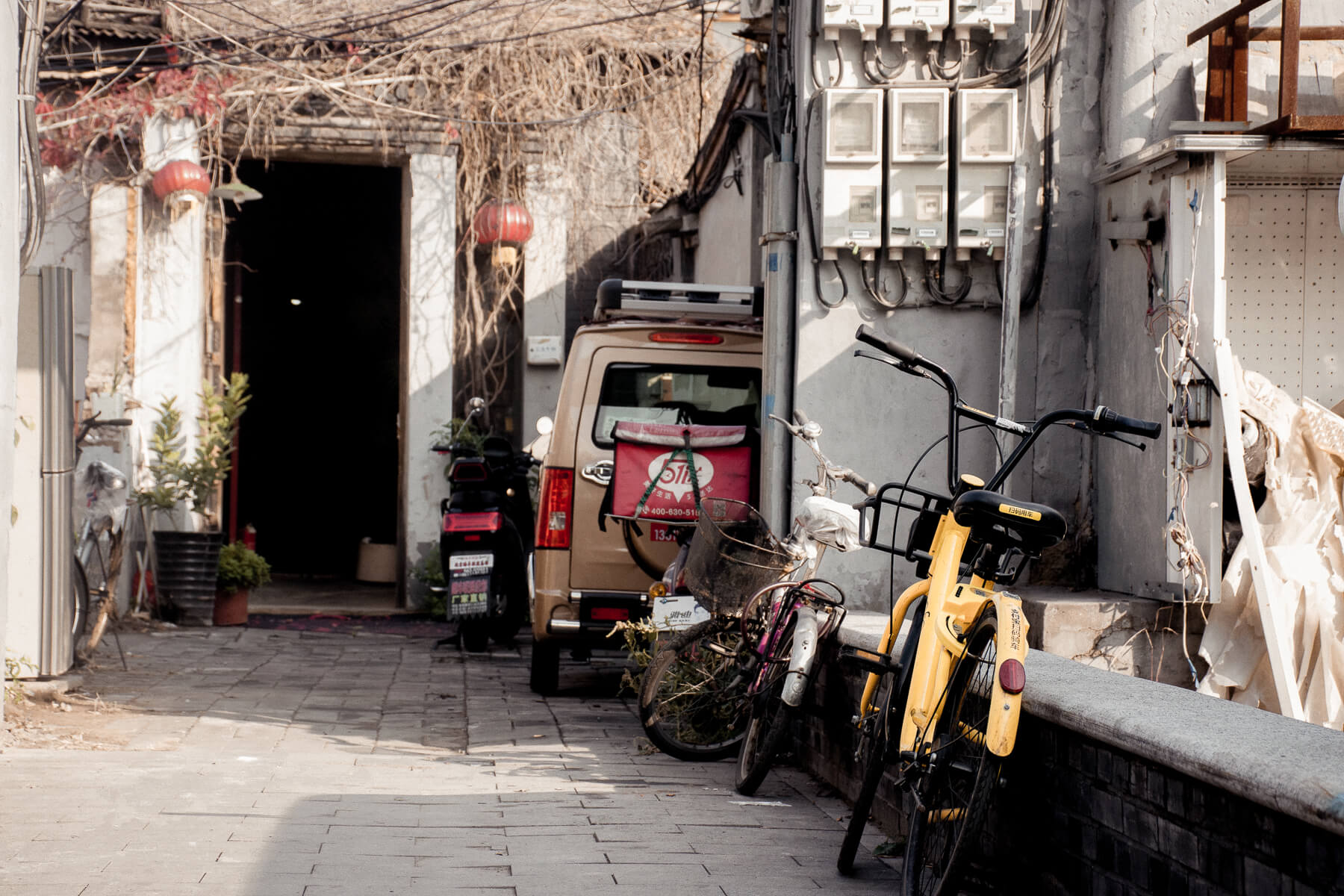 Bicycles and tuktuks leant up against a wall in Beijing's Hutong