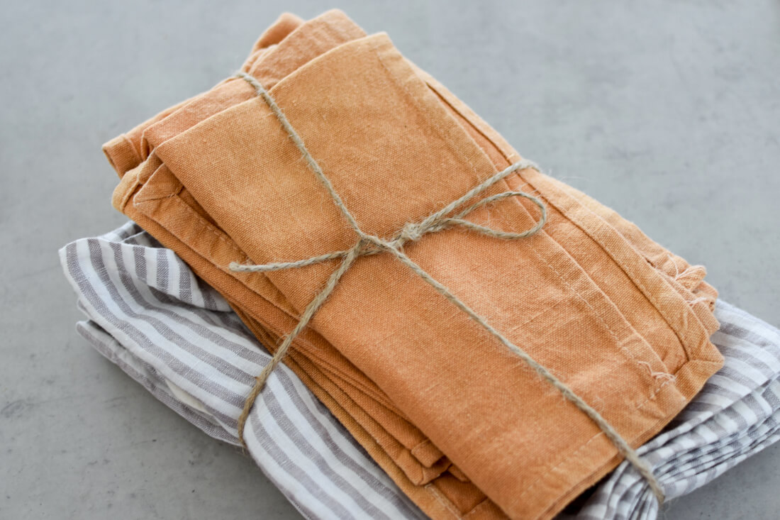 A set of grey striped and mustard yellow reusable napkins, tied up with twine