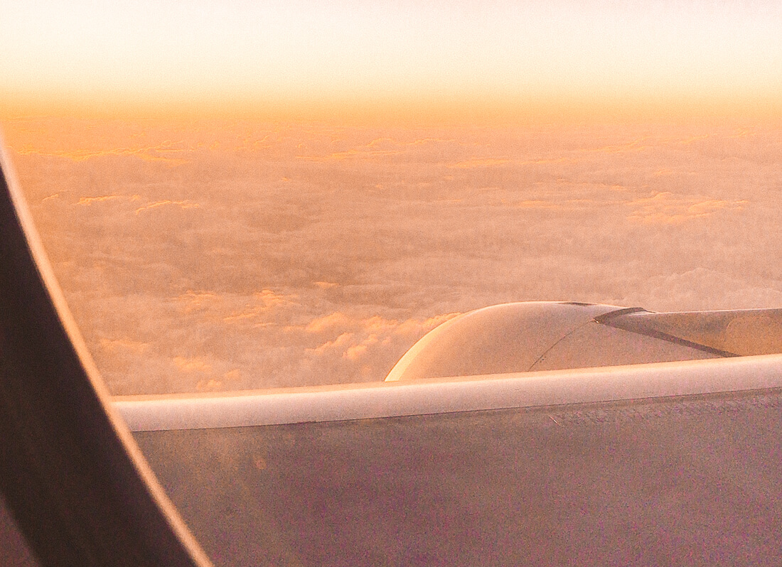 Looking out a plane window at a golden sunset above the clouds