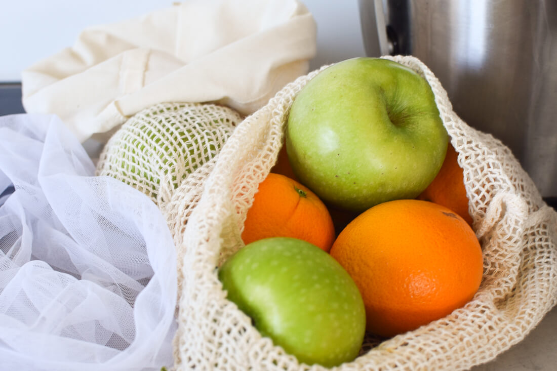 Reusable produce bags filled with apples and oranges