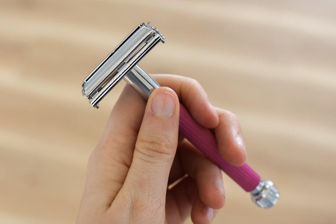 Hand holding a pink safety razor, a great zero waste alternative