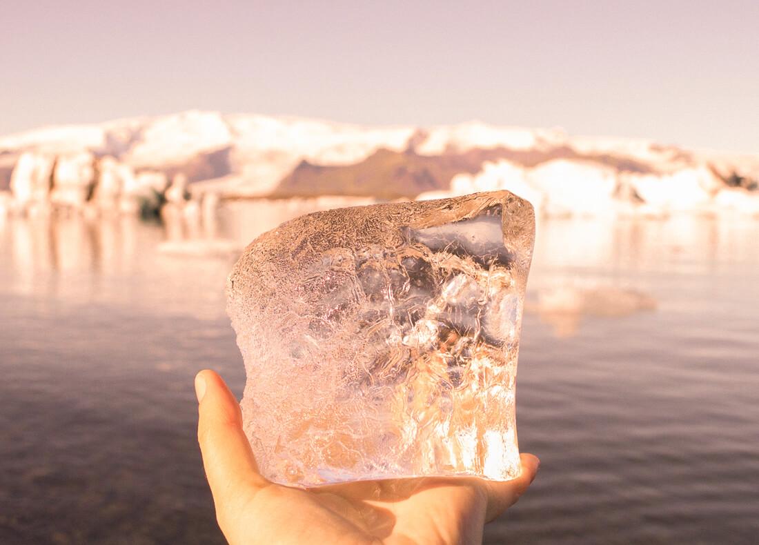 Hand holding ice block from Jokulsarlon glacier lagoon