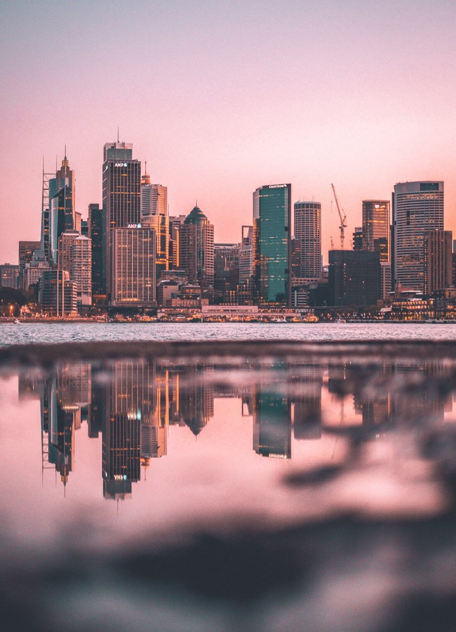 Pink sunset over city skyline with high-rise buildings reflecting in water