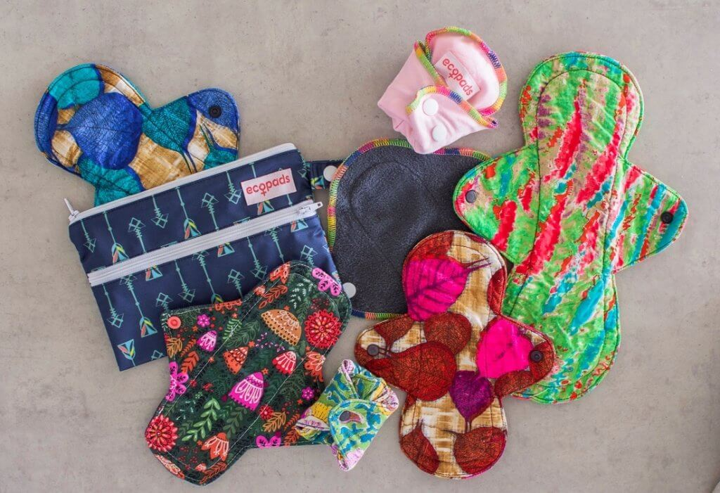 Flat lay of reusable menstrual pads and a wet bag. All different colours, patterns and sizes.