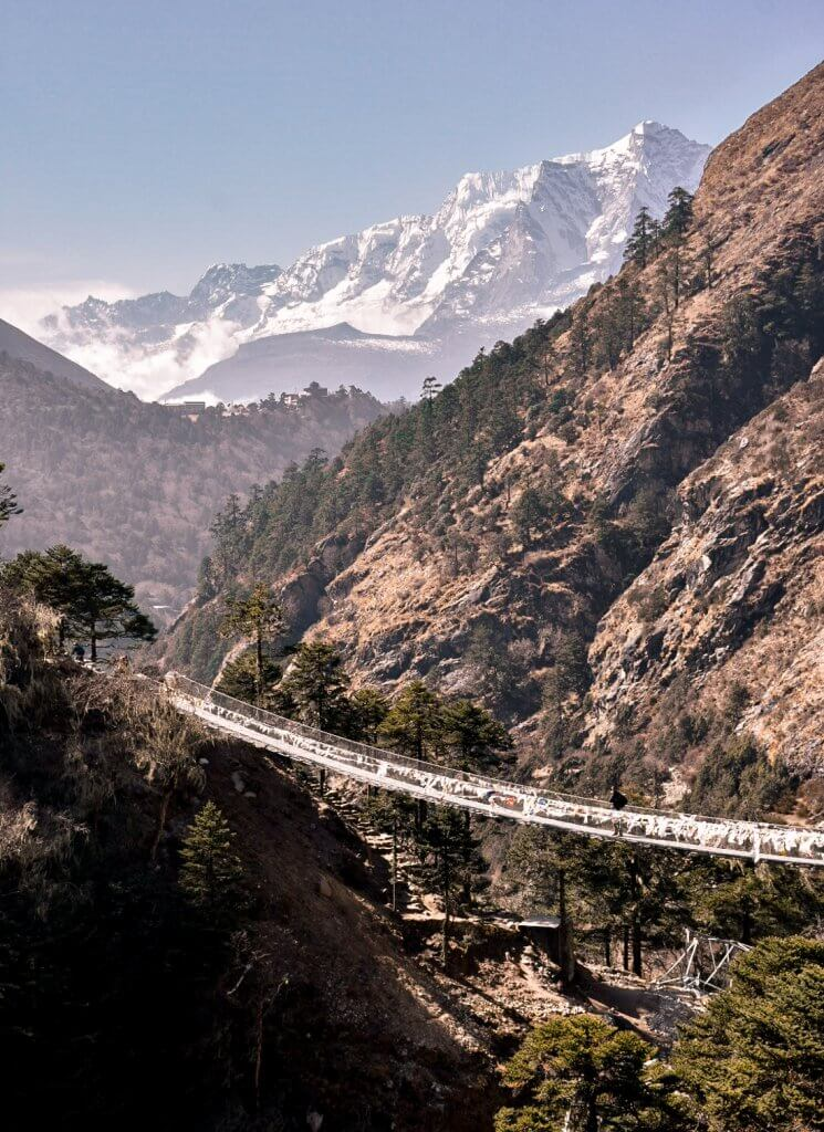 A suspension bridge crossing over a canyon, with snowy mountain in the distance - Everest Base Camp Trek.