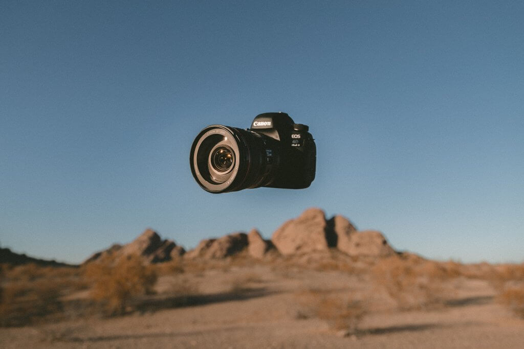 Canon camera and lens floating in the sky above some desert rocks